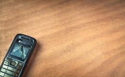 Łamany stary telefon komórkowy na drewnianym tle Zdjęcia Royalty Free