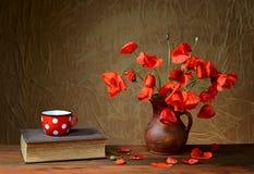 Amapolas rojas en un florero de cerámica, libros y potes del metal Foto de archivo libre de regalías