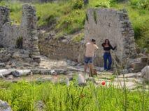 Amapolas rojas en un fondo borroso de los turistas que toman im?genes al lado de ruinas antiguas fotografía de archivo