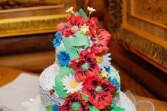 Amapolas rojas hermosas en un pastel de bodas adornado Fotografía de archivo libre de regalías