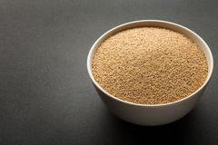 Amaranth seeds in ceramic bowl isolated on dark Stock Photo