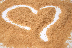 Amaranth seeds in a heart shape  on white background-close up. Stock Photos