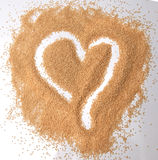 Amaranth seeds in a heart shape  on white background - top down view. Stock Photo