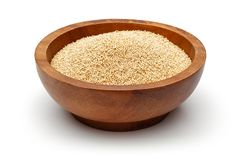 Amaranth seeds in wooden bowl. Isolated on white background stock photography