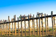 AMARAPURA,缅甸- 11月:未认出的人民在U Bein桥梁走在11月的日落,在Amarapura,缅甸 U 免版税库存照片