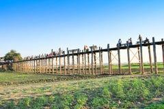 AMARAPURA,缅甸- 11月:未认出的人民在U Bein桥梁走在11月的日落,在Amarapura,缅甸 U 库存图片