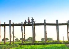 AMARAPURA,缅甸- 11月:未认出的人民在U Bein桥梁走在11月的日落,在Amarapura,缅甸 U 图库摄影