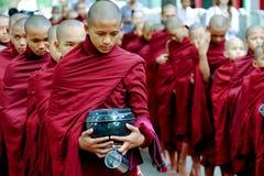 AMARAPURA, МЬЯНМА - 28-ОЕ ИЮНЯ 2015: Очередь буддийских монахов для обеда в Мьянме Стоковые Фото