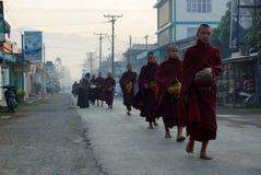 AMARAPURA, MYANMAR - 15-ОЕ ЯНВАРЯ: Буддийская прогулка послушников для того чтобы собрать a Стоковые Фотографии RF