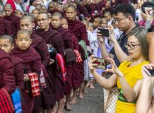 AMARAPURA, MYANMAR - 12 DE ENERO DE 2018: Los monjes que viven en el monasterio de Mahagandayon salen recibir la comida fotografía de archivo