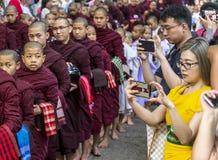 AMARAPURA, MYANMAR - 12. JANUAR 2018: Mönche, die im Mahagandayon-Kloster leben, kommen heraus, Lebensmittel zu empfangen Stockfotografie