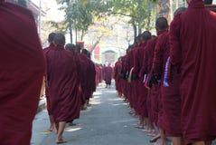 AMARAPURA, MYANMAR - 15 JANVIER : Promenade bouddhiste de novices pour rassembler a Image stock