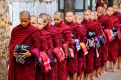 AMARAPURA MYANMAR - JUNI 28, 2015: Kö för buddistiska munkar för lun Royaltyfri Foto