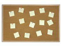 Amarele as notas de post-it tacheadas na placa da cortiça Fotos de Stock