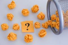 Amarele bolas de papel amarrotadas e desenrolar do ponto de interrogação de um t Fotos de Stock Royalty Free