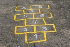 Amarelinhas criançolas do jogo no asfalto Foto de Stock