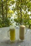 Amarelo brilhante e milks shake nos vidros com punhos e tubules em uma tabela de mármore branca em um fundo borrado de árvores ve fotos de stock