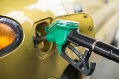 Amarelo, carro do ouro em um posto de gasolina que está sendo enchido com o combustível imagens de stock