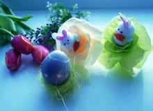 Amarelo e azul tingiu ovos, tulipas e lebres de easter para o feriado da Páscoa imagem de stock