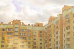 Amarelo moderno da casa do tijolo do multi-andar, o canto interno de uma construção residencial com balcões, contra o céu com imagem de stock royalty free