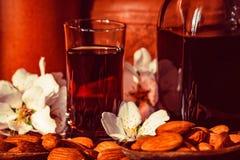 Amaretto利口酒、干杏仁和白花 免版税图库摄影