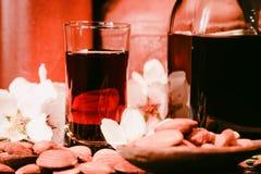 Amaretto利口酒、干杏仁和白花 图库摄影