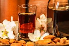 Amaretto利口酒、干杏仁和白花 免版税库存图片
