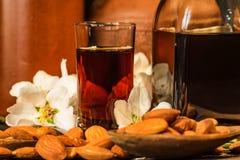 Amaretto利口酒、干杏仁和白花 免版税库存照片