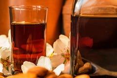 Amaretto利口酒、干杏仁和白花 库存照片