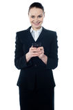 Amarican female assistant texting. Smiling at camera Royalty Free Stock Photo