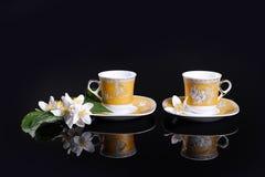 Amarillee las tazas y las flores Foto de archivo