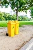 Amarillo del bote de basura en parque Foto de archivo