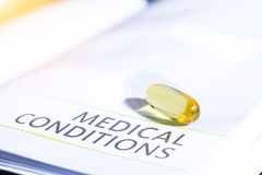 Amarillo del color de las píldoras en el libro de la medicación Imagen de archivo
