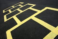 Amarillo del juego del Hopscotch en el pavimento Imagenes de archivo