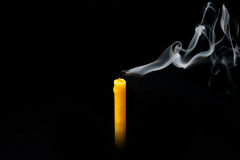 Amarillo extinguido de la vela con el humo, aislado sobre negro Imagen de archivo libre de regalías