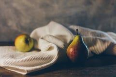 Amarillo maduro con las peras sabrosas rojas en la toalla blanca enrollada en la tabla de madera rústica del marrón oscuro y el C Imágenes de archivo libres de regalías