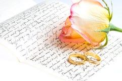 Amarillo rojo color de rosa, anillo sobre una letra escrita mano Imagen de archivo