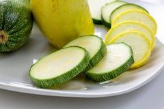 ` Amarillo y verde cortado s del calabacín en una placa blanca que se sienta en una tabla de cocina que espera para ser consumido imagen de archivo libre de regalías