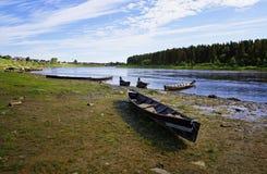 Amarrado à costa perto da vila de barcos de madeira clássicos longos dos povos Siberian de Mansi Imagem de Stock Royalty Free
