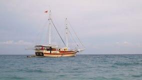 Amarrando gulet turístico con las banderas turcas y las velas bajadas, cerca de la costa costa mediterránea almacen de metraje de vídeo