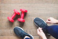 Amarrando sapatas do esporte, mulher asiática que prepara-se para o treinamento do peso Exercício, treinamento da aptidão Estilo  foto de stock royalty free