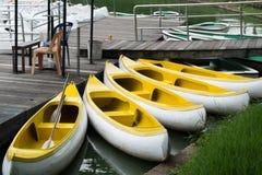 Amarre amarillo de la canoa en el puerto de madera Imagenes de archivo