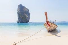 Amarre de madera del barco del longtail en la playa tropical con el símbolo de la roca de la piedra caliza del krabi Tailandia de Foto de archivo libre de regalías