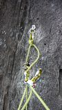 Amarre la postura para la escalada en granito negro con mosquetones de los pernos y una cuerda amarilla fotografía de archivo libre de regalías