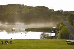 Amarrez le noir à quai de vert jaune d'été de coucher du soleil de brouillard de lac image libre de droits