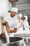 Amasadora de Pouring Flour In del panadero de sexo masculino feliz fotos de archivo