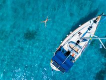 Aerial view to Yacht in deep blue sea. Drone photography. Amasing aerial view to Yacht in deep blue sea with swimming girl. Drone photography stock photography