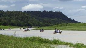 Amasonregnskogen som folk går i floden för fartyg ner stock video