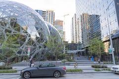 Amasonvärlden förlägger högkvarter sfärer med parkerade bilar och gångare Arkivbild