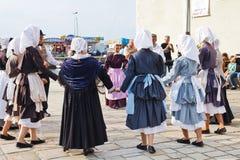 Amatörer i nationella klänningar som dansar breton dans Arkivfoto